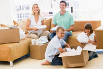 Photograph of happy family unpacking boxes